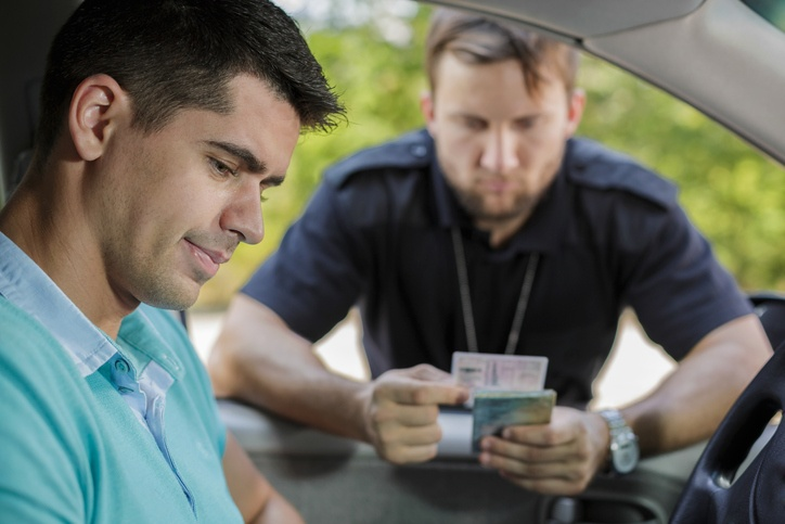 Shot of a young driver and a policeman checking his driving licence