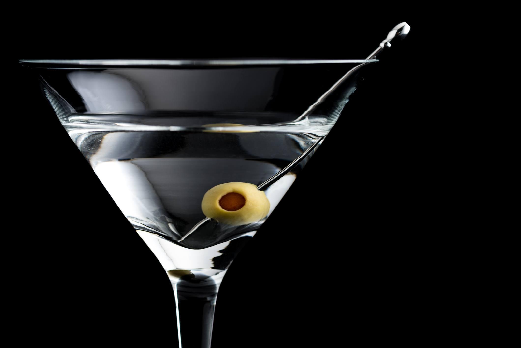 Vodka martini cocktail with olives on black background