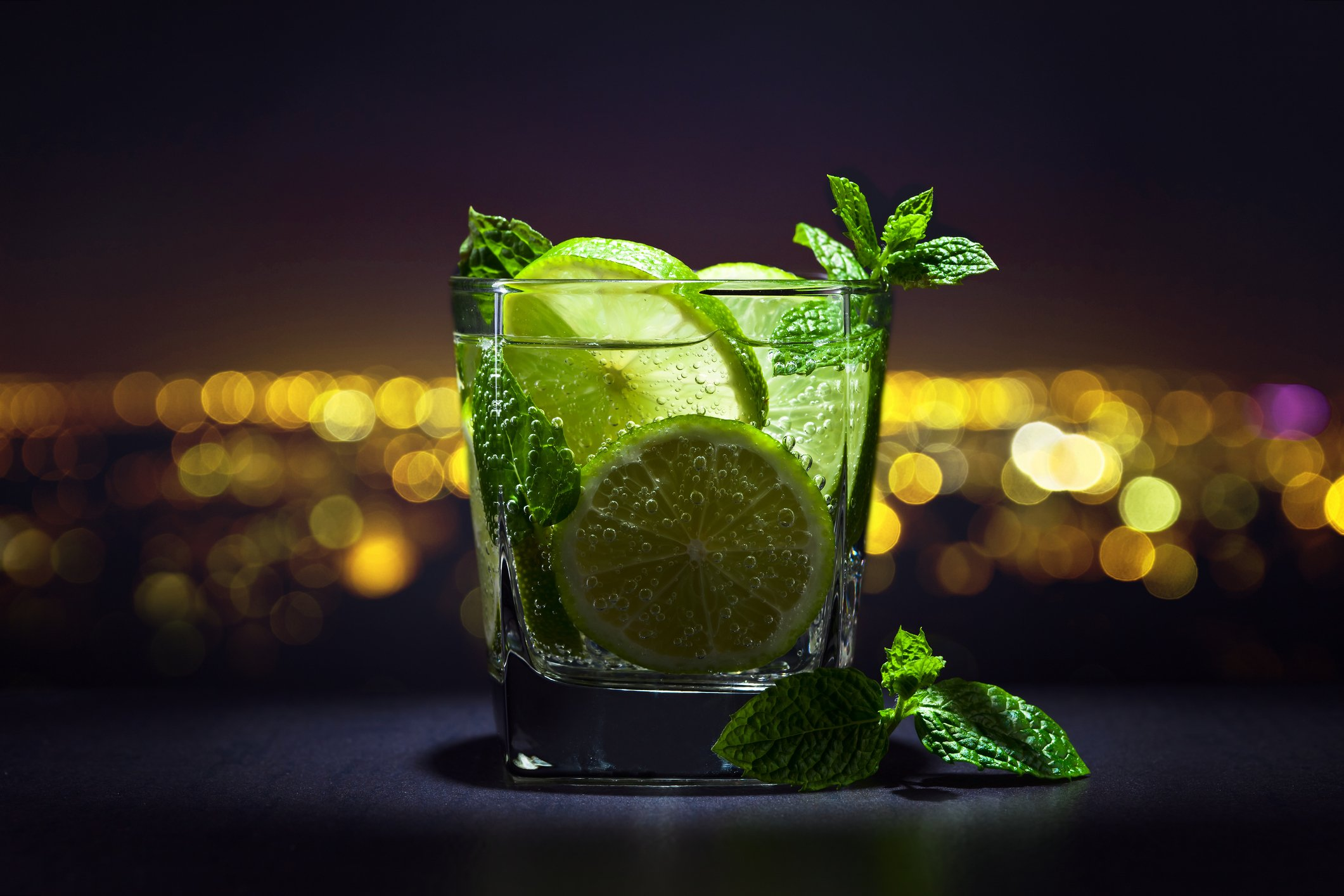 Drink with lime , ice and peppermint leaves on a background of night city