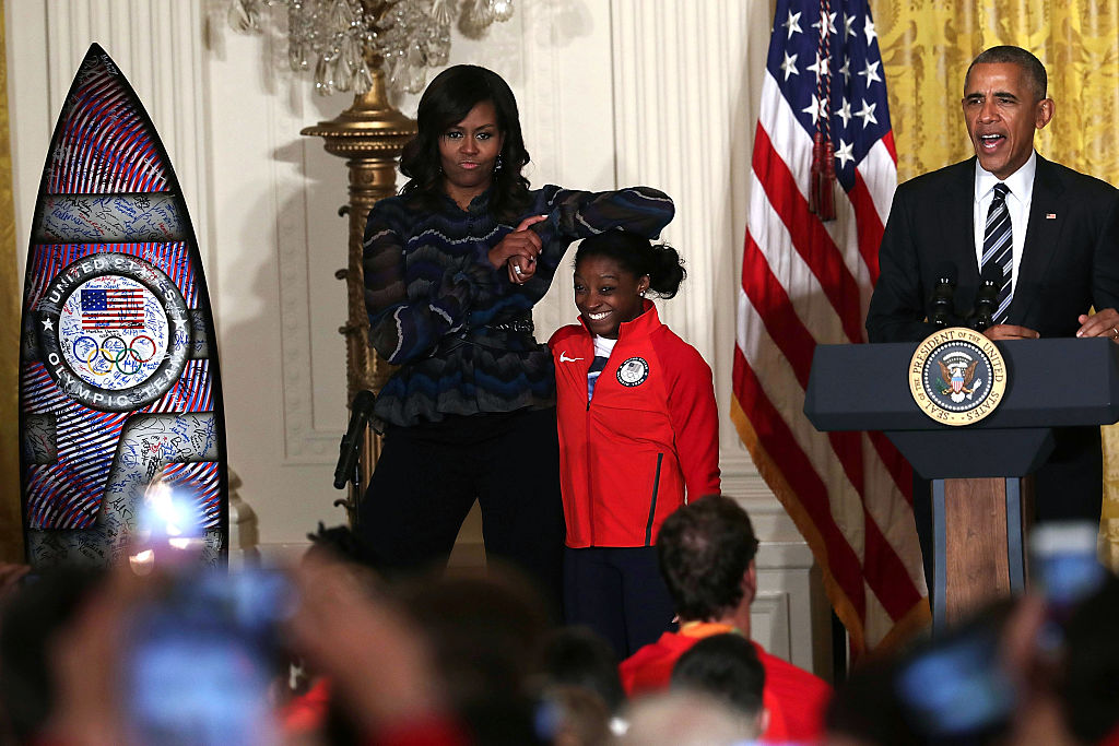 Michelle Obama rests her elbow on the head of Olympian Simone Biles