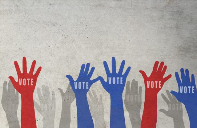 Multi colored hands drawn raising towards the sky with vote written in the image.
