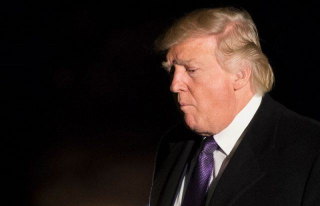 Donald Trump standing in front of a dark background.