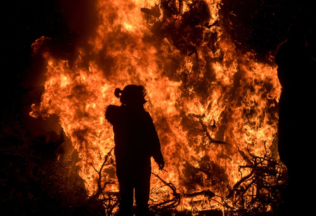a woman in front of a raging bonfire