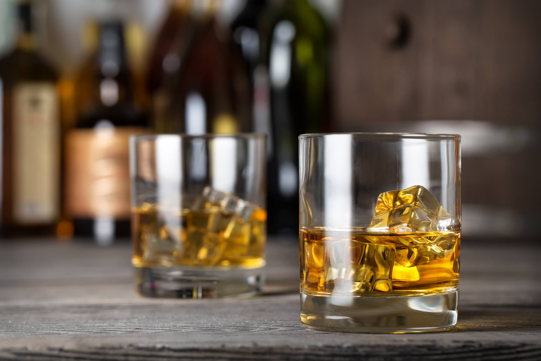 Two glasses of whiskey with ice on the bar counter against the bottles
