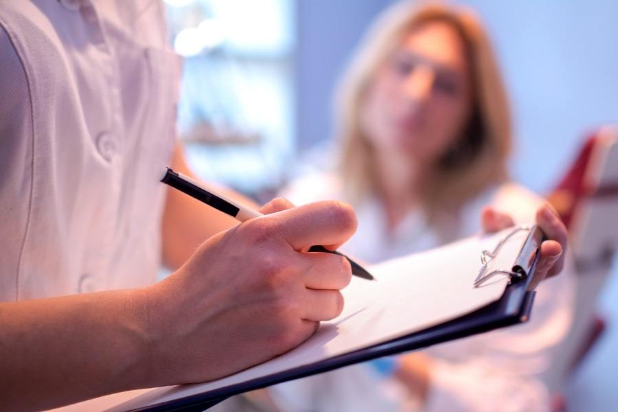 doctor writing on a medical chart.