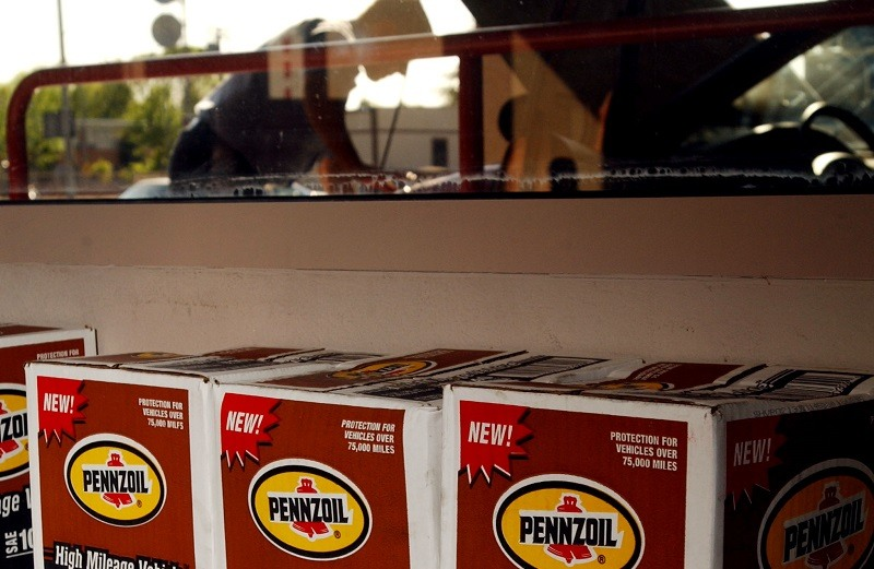 Boxes of Pennzoil motor oil are stacked near an employee of Jiffy Lube, a company owned by Pennzoil-Quaker State Co., changing performing an oil change March 26, 2002 in Los Angeles, CA. Anglo-Dutch oil giant Royal Dutch/Shell Group announced this week that it will acquire Pennzoil-Quaker State Co., maker of the top two motor oil brands in the United States, for $1.8 billion in cash.