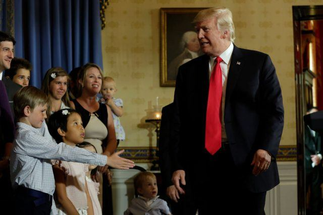 """Trump talks to children of alleged """"victims of Obamacare"""" after delivering a statement on healthcare at the White House."""