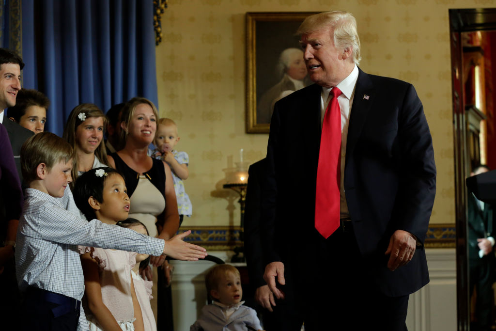 "Trump talks to children of alleged ""victims of Obamacare"" after delivering a statement on healthcare at the White House"