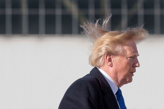 US President Donald Trump's hair blows in the wind as he boards Air Force One