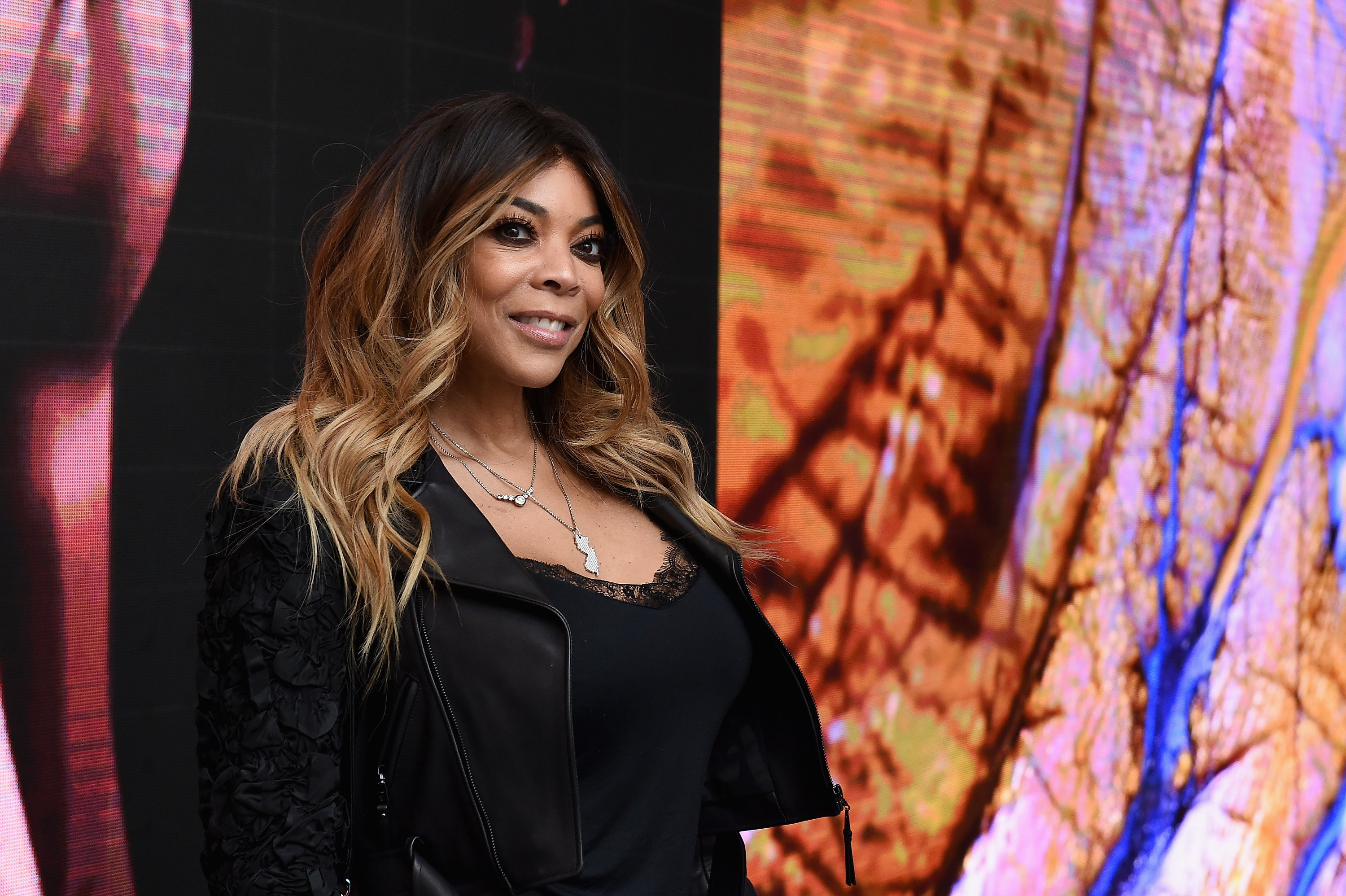 Wendy Williams smiles and wears a black outfit