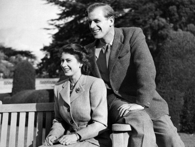 Queen Elizabeth II and Prince Phillip posing and smiling on a bench.