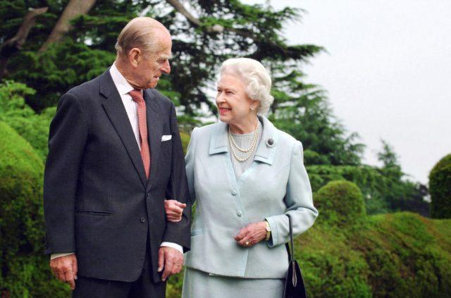 Queen Elizabeth and Prince Phillip standing together outdoors.
