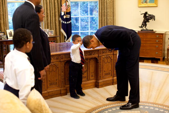 Obama bends over so the son of a White House staff member can pat his head during a visit to the Oval Office