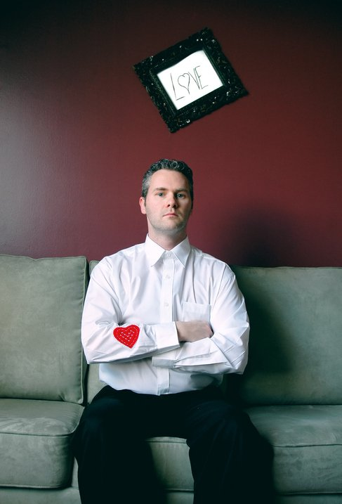 man on couch with heart on sleeve