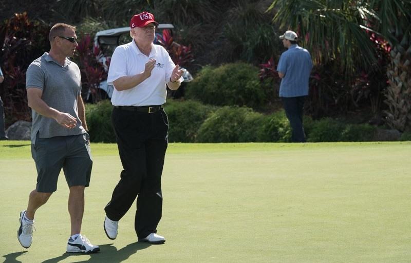 Trump walking across a golf course