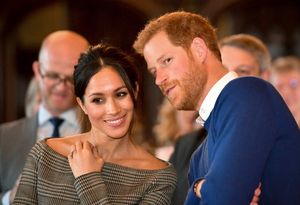 Prince Harry whispers to Meghan Markle