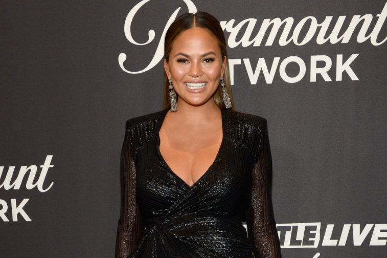 Chrissy Teigen wearing a black dress.