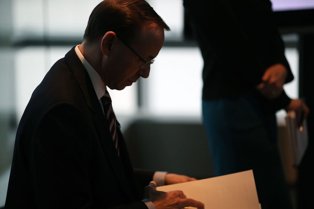 rod rosenstein looks over a stack of papers in profile