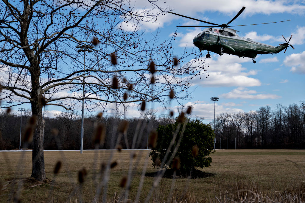 a military helicopter landing in a field