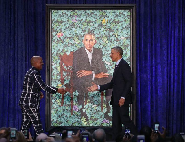 Former U.S. President Barack Obama stands artist Kehinde Wiley next to his newly unveiled portrait during a ceremony at the Smithsonian's National Portrait Gallery in Washington, DC.