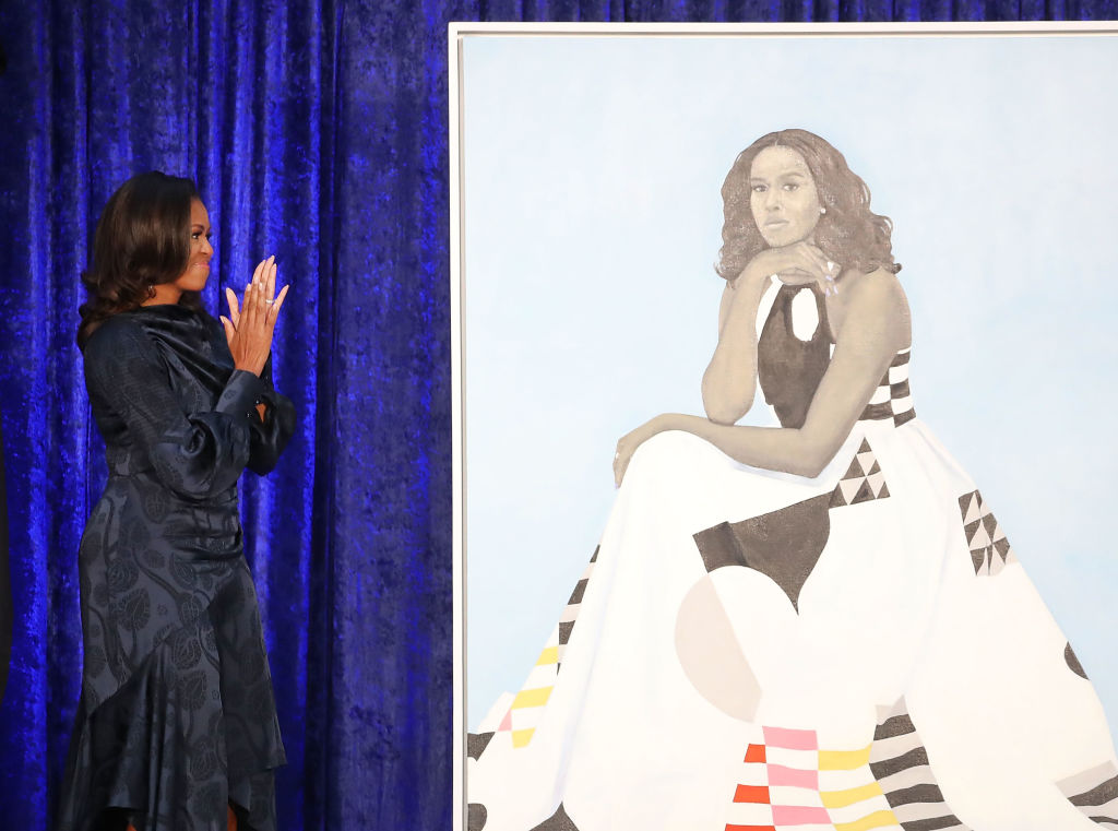 Former U.S. first lady Michelle Obama looks at her newly unveiled portrait during a ceremony at the Smithsonian's National Portrait Gallery, on February 12, 2018 in Washington, DC.