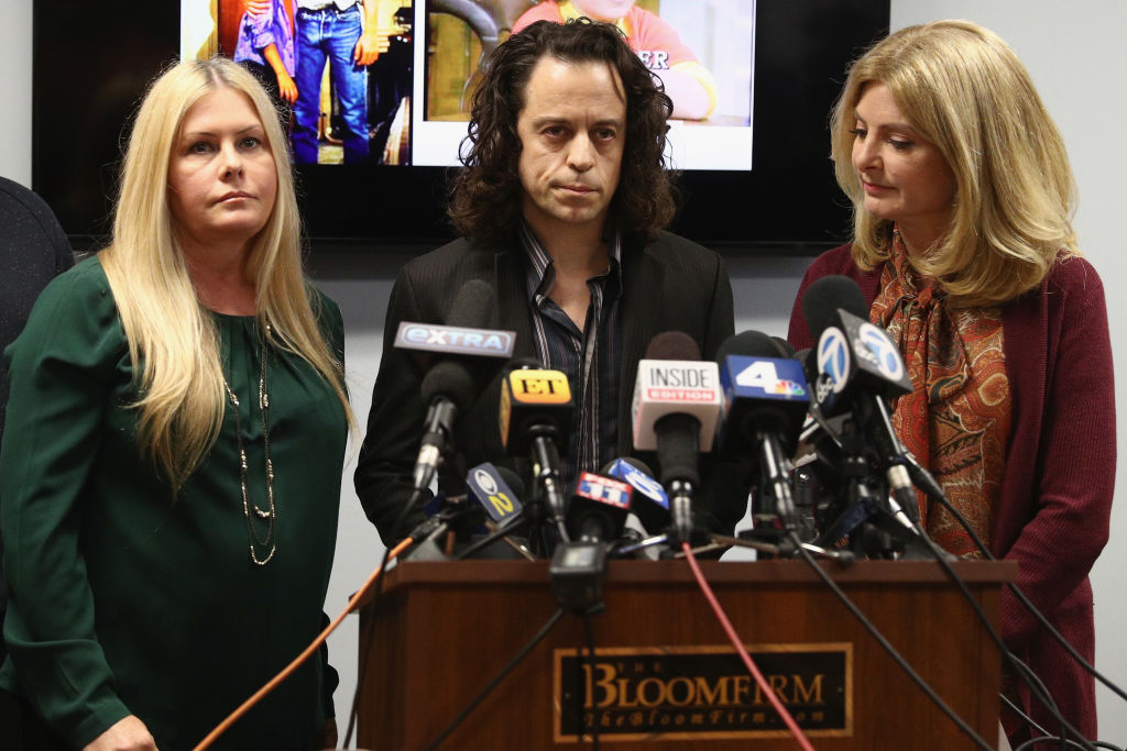 """Alexander Polinsky speaks during a press conference with Nicole Eggert (L) and his attorney Lisa Bloom regarding sexual harassment allegations against Scott Baio at The Bloom Firm on February 14, 2018 in Woodland Hills, California. Polinsky is the second person, along with Nicole Eggert, to costarred with Baio in the 1980's sitcom """"Charles in Charge"""" who have accused him of sexual harassment. Both Polinsky and Eggert were minors at the time."""