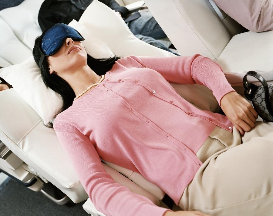 Woman sleeping in airplane with eye mask