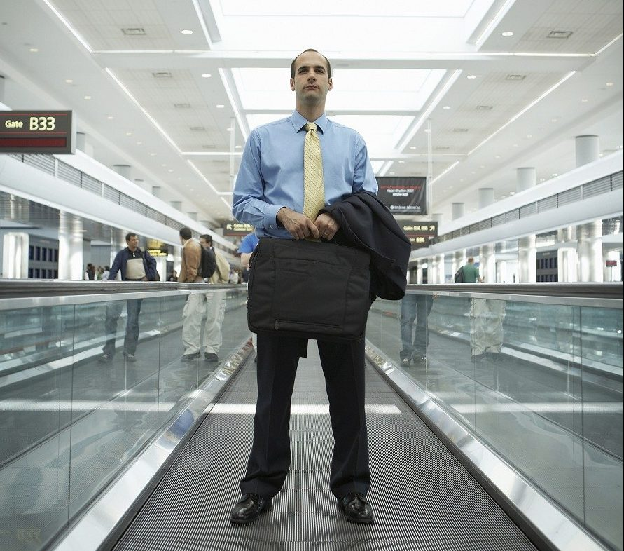 man at airport, carrying briefcase and jacket