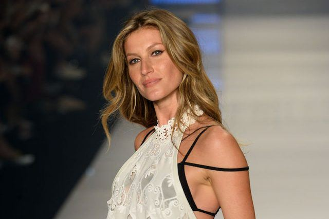 Gisele smiles as she poses on a fashion runway.