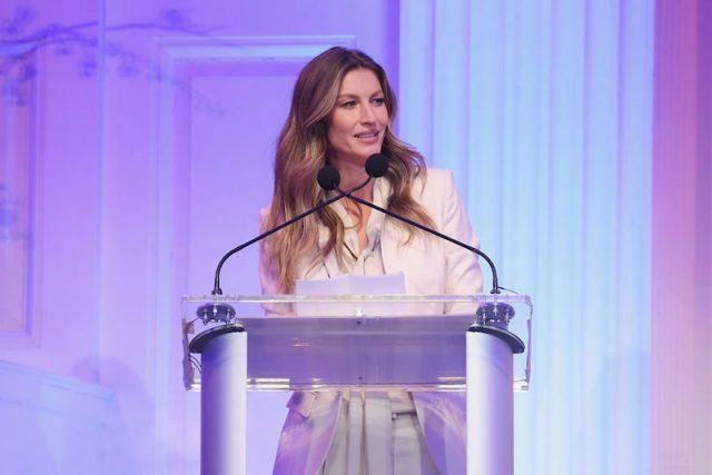 Gisele Bundchen speaking behind a podium.