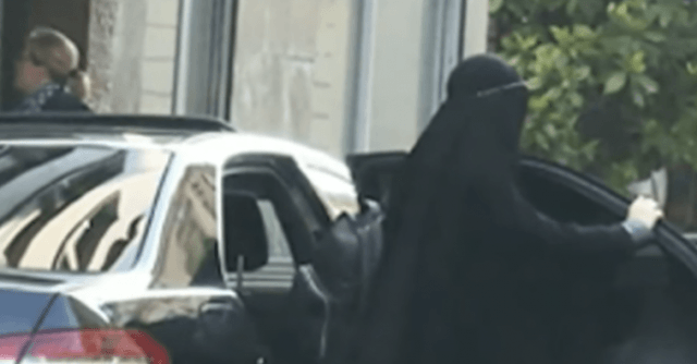 Gisele emerges from a black car dressed in a burqa.