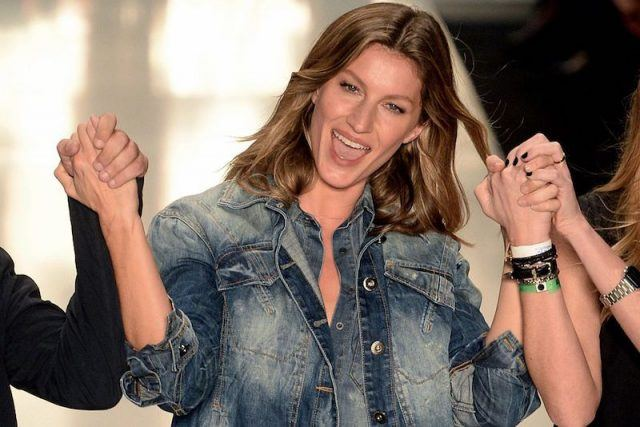 Gisele cheering as she walks on a fashion runway.
