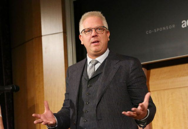 Glenn Beck speaking as he holds out his hands on stage.