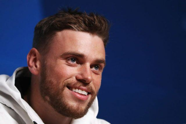Gus Kenworthy smiling while wearing a white hoodie.