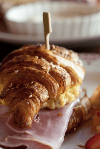 A croissant with eggs and ham.
