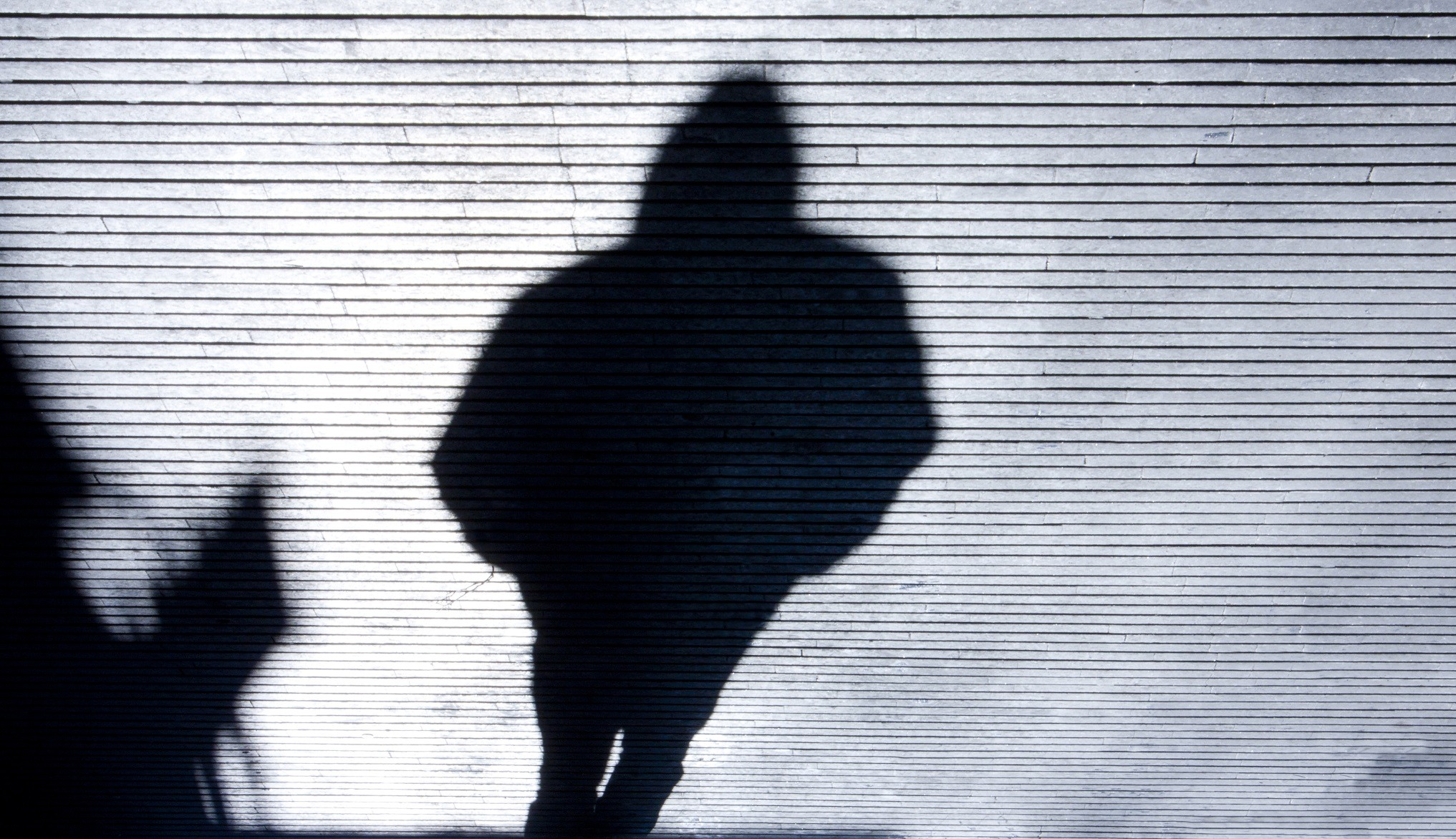 Shadow of person walking with hands in pockets and hood up