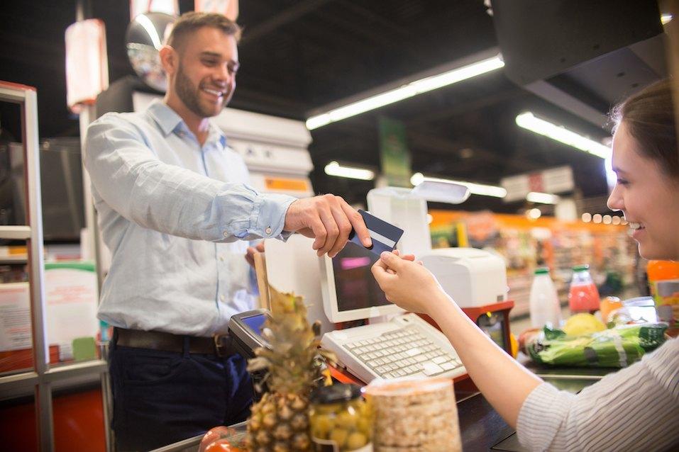 Happy Man Handing Credit Card to Cashier in Supermarket