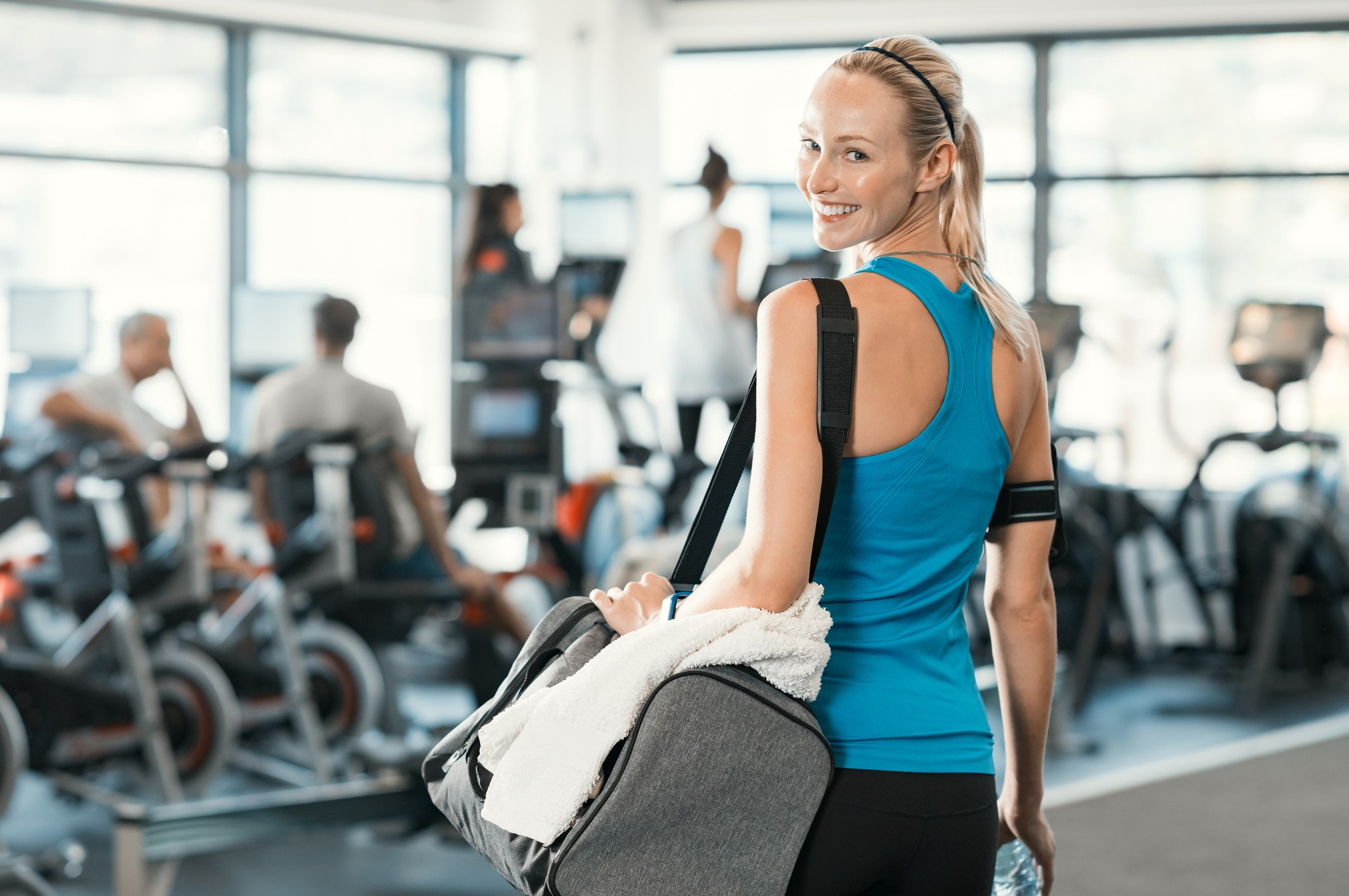 woman holding gym bag in a fitness centre.