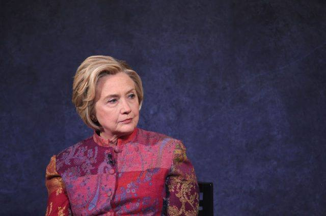 Hillary Clinton sitting on stage in a colorful suit.
