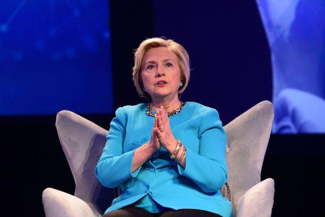 Hillary Clinton sitting in a chair on stage.