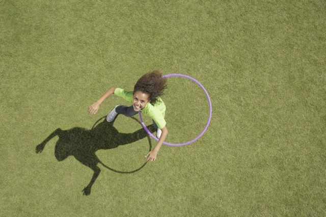 A young girl playing with a hoola hoop.
