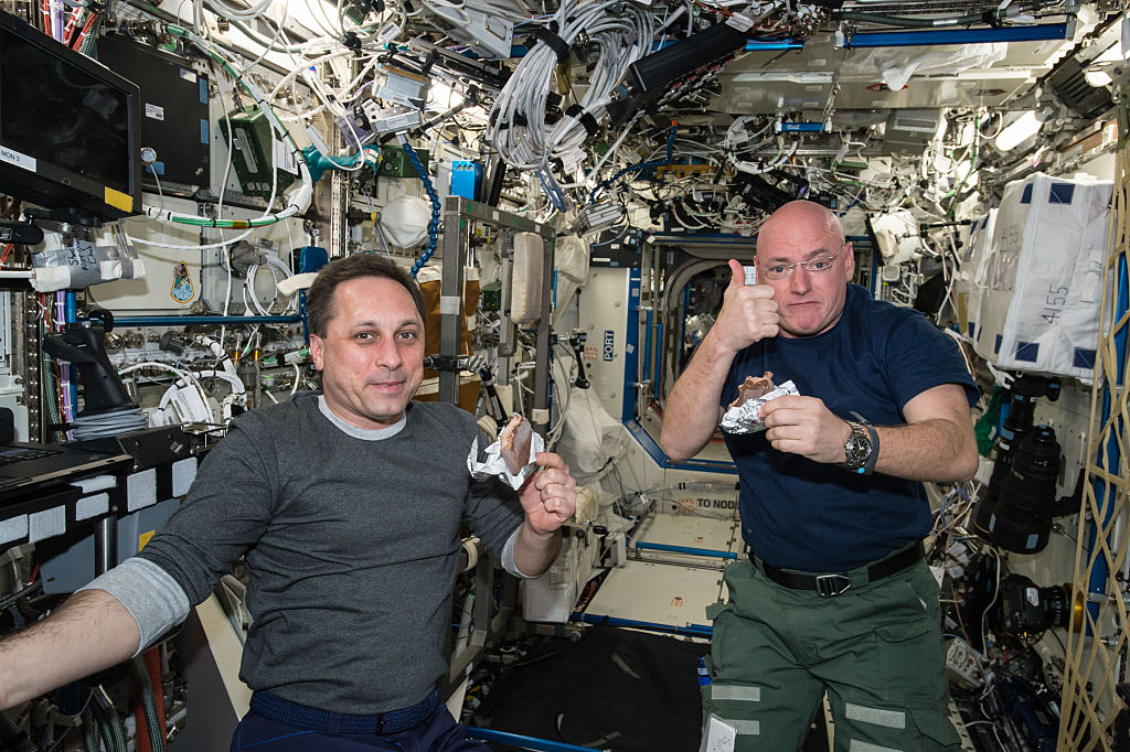 NASA astronaut Scott Kelly gives a thumbs up on the quality of his snack while taking a break from his work schedule