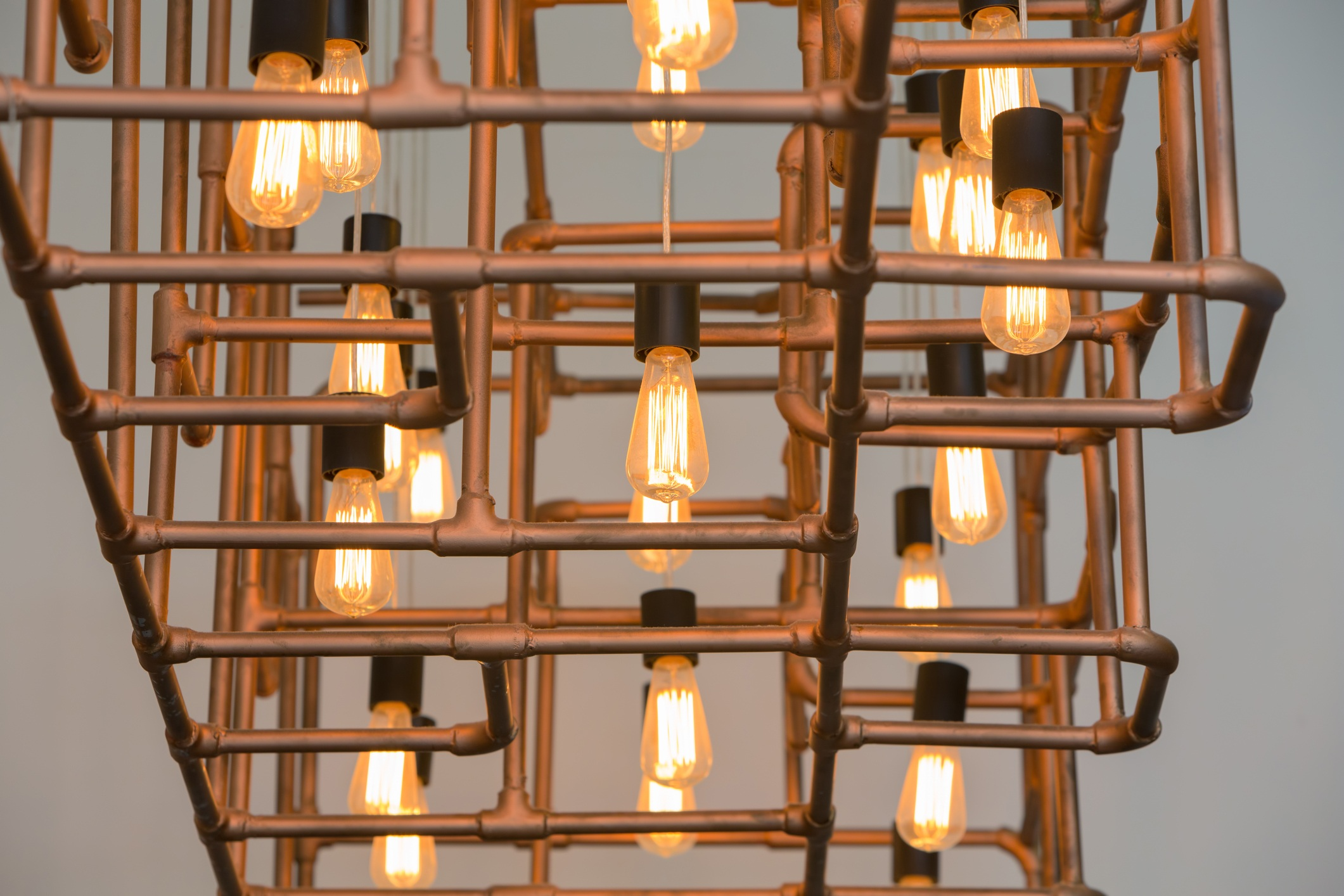 Vintage style light bulbs hang and decorated with alloy pipes in a living room
