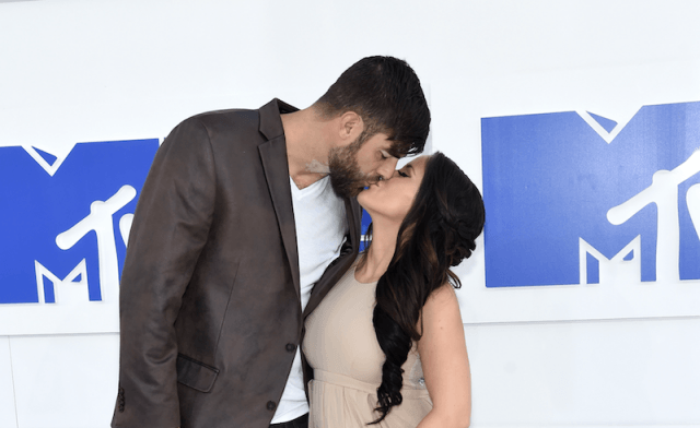 Jenelle Evans and David Eason kissing on a red carpet.