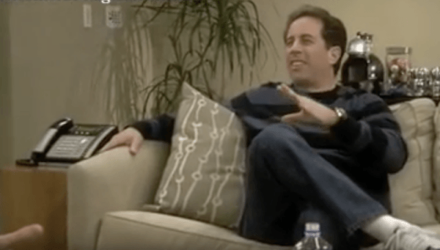 Jerry Seinfeld sitting on a sofa talking to Larry David.