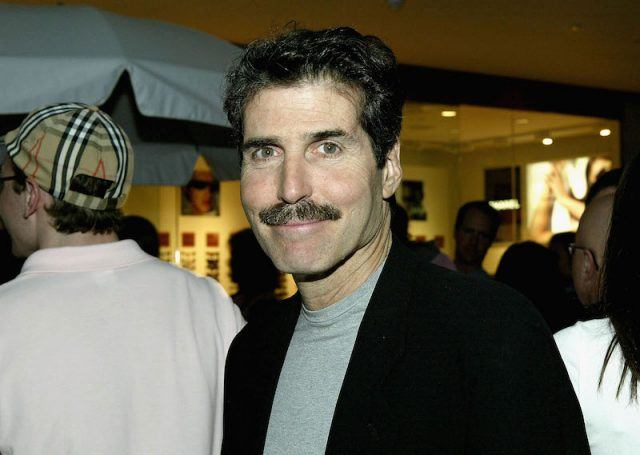 John Stossel smiling while posing for a photographer.