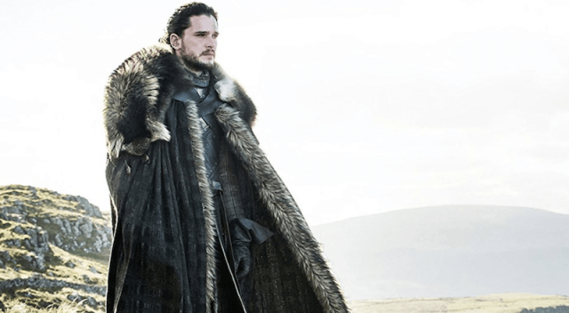 Jon Snow stands looking over a cliff.