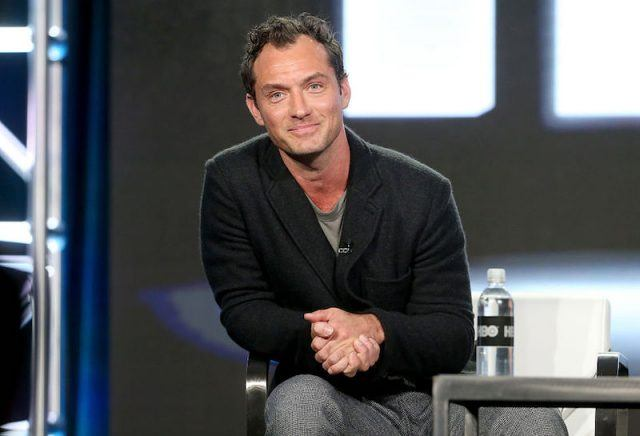 Jude law sits and smiles while on an on-stage panel.