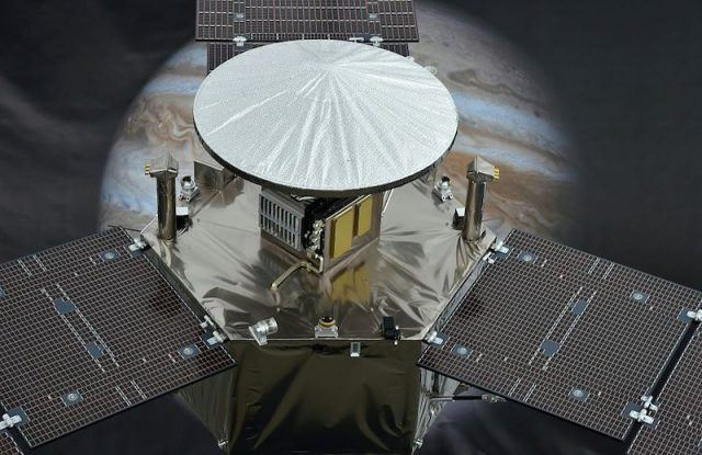 The spacecraft in front of an image of Jupiter.