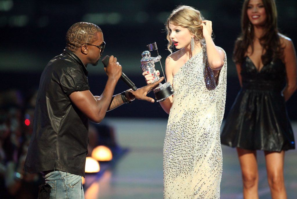 """Kanye West (L) jumps onstage after Taylor Swift (C) won the """"Best Female Video"""" award during the 2009 MTV Video Music Awards at Radio City Music Hall"""